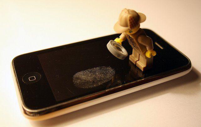 Une empreinte de doigt sur un téléphone portable, scrutée par une figurine tenant une loupe.