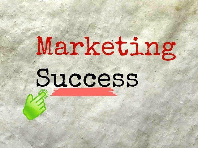 """Papier sur lequel il écrit """"marketing success"""", ou """"succès marketing"""", en français."""