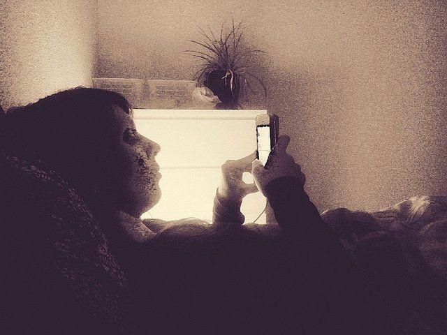 Une personne allongée regardant son écran de téléphone.