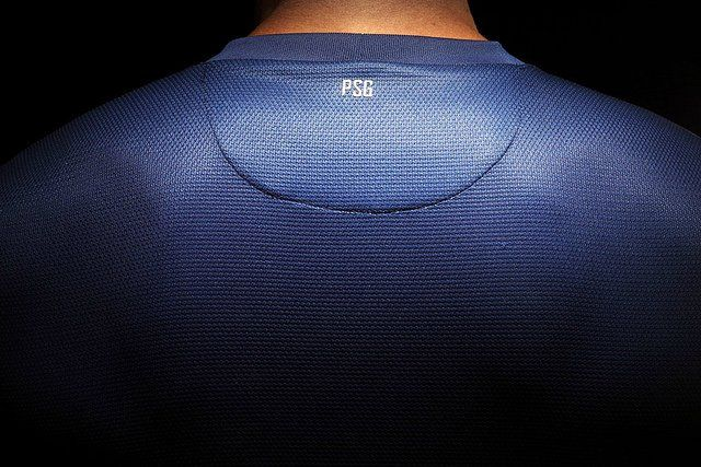 Homme portant le maillot du PSG de dos.