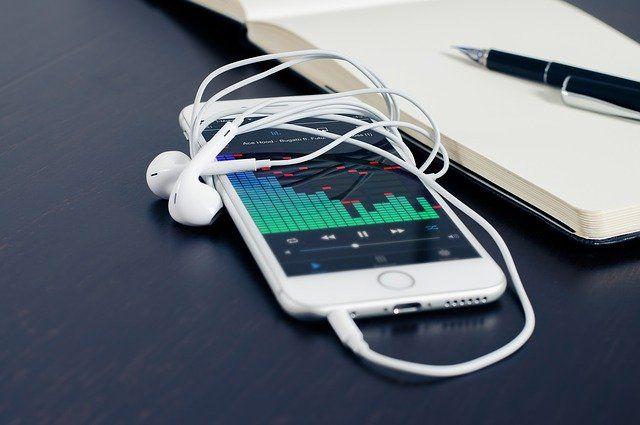 Smartphone avec écouteurs et cahier à côté.