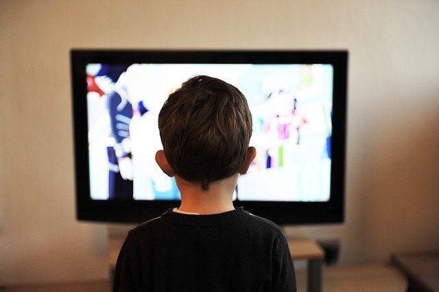 Un petit garçon devant un écran de télévision.