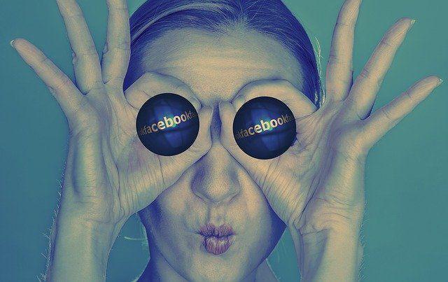 Une femme tient deux boules sur ses yeux, sur lesquelles il est écrit Facebook.