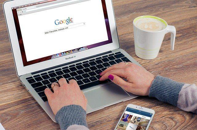 Des mains de femmes tapant sur un clavier d'ordinateur. Sur l'écran, la page Google est ouverte.