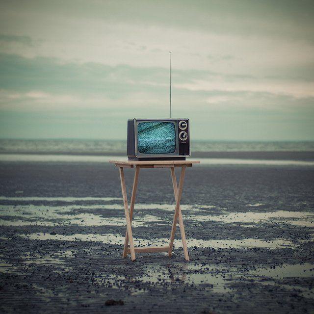 Télévision ancienne posée sur un support en bois.