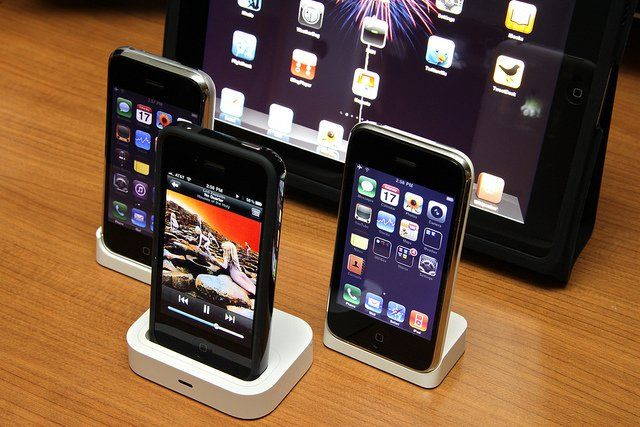 Des iPhone et un iPad disposés sur une table.