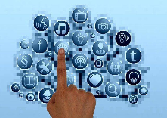 Un doigt sur un écran qui appuie sur des icônes affichant une note de musique, un cœur, des outils de bricolage ou encore le logo Facebook.