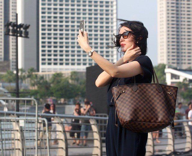 Une femme portant des lunettes de soleil réalise un selfie.
