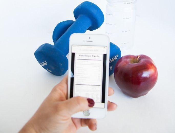 Un smartphone devant des petites haltères et une pomme.