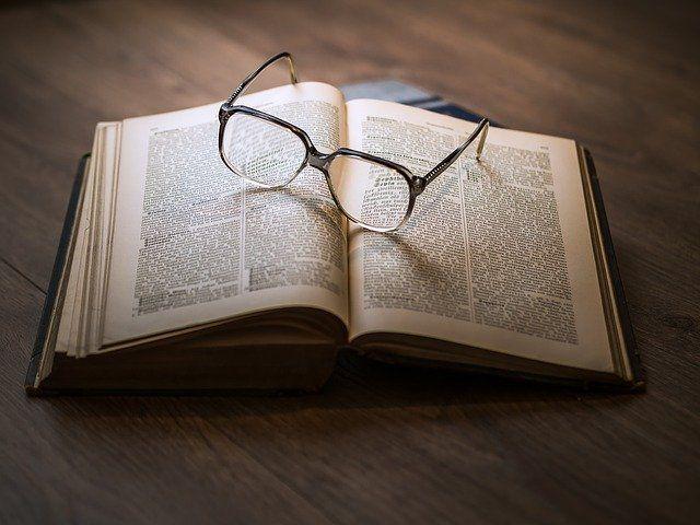 Un livre ouvert et des lunettes de vue posées dessus.