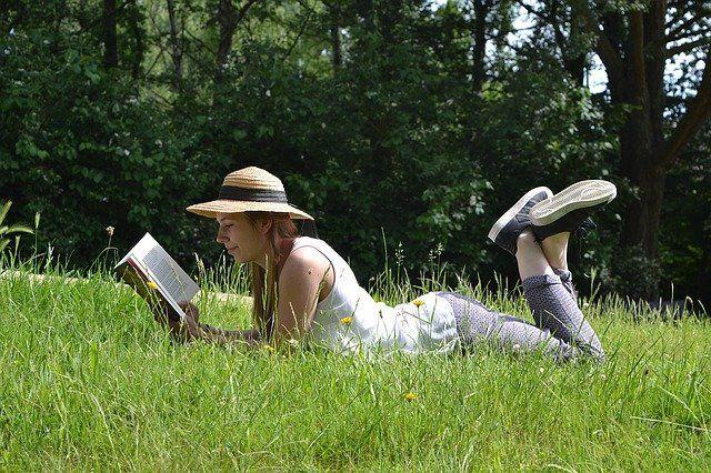 Jeune femme portant un chapeau allongée dans l'herbe et lisant un livre.