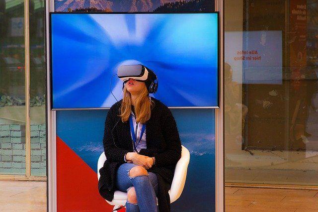 Femme assise avec un casque de réalité virtuelle sur les yeux.