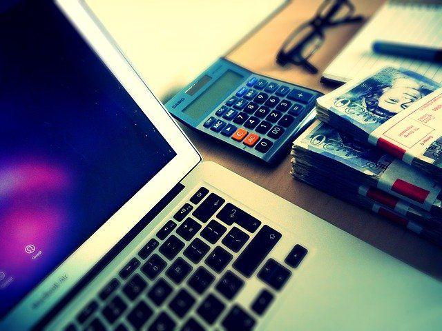 Liasses de billets de banque près d'un ordinateur et d'une calculette, en vue de faire des achat sur le web.