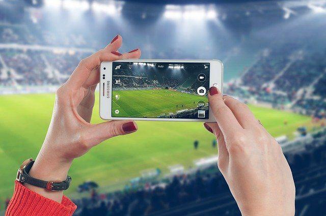 Mains de femme tenant un smartphone devant un stade de football.